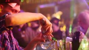 Le barman jette la glace en verres à une barre dans la boîte de nuit serrée Mouvement lent strobe clips vidéos