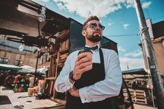 Le barman ? la mode toilett? en verres a une pause-caf? et caf? de appr?cier images libres de droits