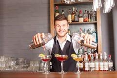 Le barman masculin gai mélange la boisson dans la barre photographie stock libre de droits