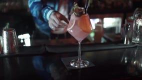 Le barman met dessus le cocktail de la table A avec la chaux et la menthe dans le verre banque de vidéos