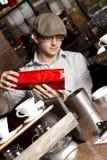 Le barman pleut à torrents des grains de café dans le conteneur Photo libre de droits