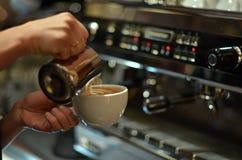 Le barman prépare le latte de café Dans la perspective d'une machine de café Photographie stock