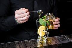 Le barman prépare le thé de fruit avec des canneberges à un arrière-plan en verre et foncé image stock
