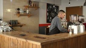 Le barman prépare un latte parfumé dans un café, il met du café sur la barre banque de vidéos
