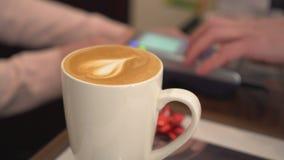 Le barman prend la carte de crédit Café avec un coeur dans la tasse Plan rapproché Photo stock