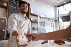 Le barman prend le paiement par carte de crédit à un café, fin photographie stock