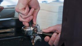 Le barman presse le cafè moulu utilisant le bourreur