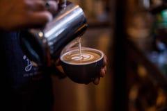 Le barman professionnel dessine l'art de latte sur la tasse de café photo libre de droits