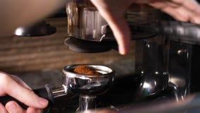 Le barman rectifie le café avec une broyeur de café de main banque de vidéos