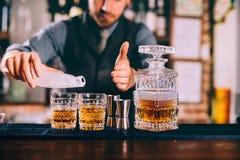 le barman remet ajouter la glace et le whiskey aux cocktails urbains modernes Barre de ciel servant les boissons élégantes photo libre de droits