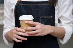 Le barman remet tenir une tasse de café d'emporter avec au counte de café image libre de droits