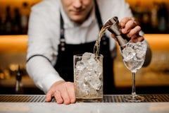 Le barman s'est habillé dans une chemise blanche versant la boisson alcoolisée dans un verre avec des glaçons Photographie stock
