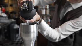 Le barman serre le jus au dispositif trembleur de cocktail, faisant des cocktails, barman au travail, au compteur de barre