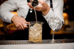 Le barman versant la boisson alcoolisée dans un grand verre a rempli de glaçons Photo stock