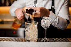 Le barman versant la boisson alcoolisée dans un verre a rempli de glaçons Photos stock