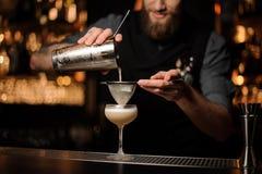 Le barman verse le cocktail ajoutant le mélange aigre en verre photographie stock libre de droits