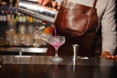 Le barman verse d'un dispositif trembleur en acier dans un verre de cocktail un cocktail de couleur lilas d'alcool photo stock