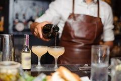 Le barman verse l'alcool d'une bouteille dans des verres de vin avec de la glace images stock
