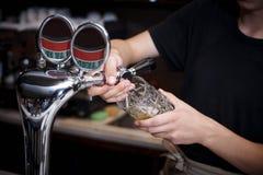Le barman verse la bière photographie stock