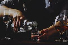 Le barman verse la vodka ou la tequila dans le petit verre ? liqueur sur le vieux compteur de barre Fond en bois de cru dans le b photographie stock libre de droits