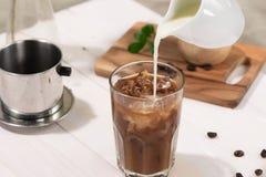 Le barman verse le lait dans le verre de café Images stock