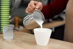 Le barman verse le lait du pot en métal dans la tasse en verre blanche sur la table en bois Latte de Prepait photo libre de droits
