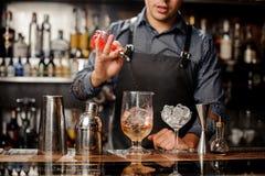 Le barman verse le sirop en verre de cocktail avec de la glace Photographie stock libre de droits