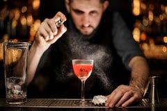 Le barman verse un cocktail d'alcool utilisant le pulvérisateur images libres de droits