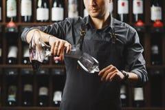 Le barman verse le vin rouge en verre de grand navire transparent photo libre de droits