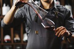 Le barman verse le vin rouge en verre de grand navire transparent photos libres de droits