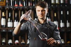 Le barman verse le vin rouge en verre de grand navire transparent images stock