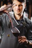 Le barman verse le vin rouge en verre de grand navire transparent photographie stock