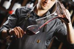 Le barman verse le vin rouge en verre de grand navire transparent image libre de droits
