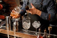 Le barman verse le whiskey et le sirop sur la glace en verre de cocktail photographie stock libre de droits