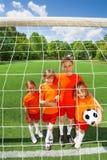 Le barn som står nära med fotboll royaltyfria foton