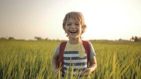 Le barnet i det gröna gräset av risfältet på väghem från skola arkivfilmer