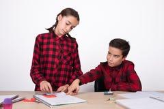 Le barnet som pekar resultatet av ett problem till en flicka i anteckningsboken royaltyfria bilder