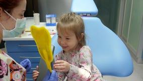 Le barnet som ser i spegelsammanträde på tand- stol bredvid doktor i medicinsk maskering arkivfilmer