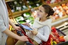 Le barnlivsmedelsbutikshopping med föräldrar royaltyfri fotografi