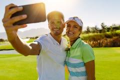 Le barnpar som tar selfie på golfbanan Royaltyfria Foton