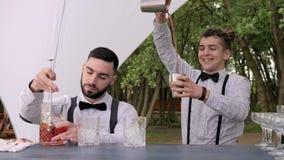 Le bartendrar bak stång, is för bartenderuppståndelsesked i exponeringsglas, hällande coctail för bartender från shaker in i blan stock video