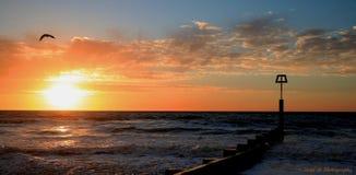 Le bas soleil plaçant au-dessus de l'océan avec le ciel orange Photos libres de droits