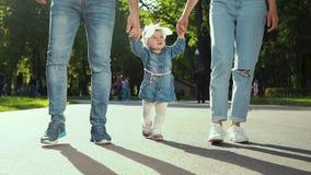 Le bas tir des parents tiennent des mains de fille d'enfant en bas âge marchant en parc ensoleillé en été clips vidéos