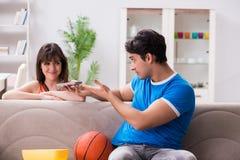 Le basket-ball de observation d'homme avec son épouse Images stock