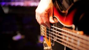 Le bassiste remet jouer la musique rock avec la guitare basse dans le concert de boîte de nuit banque de vidéos
