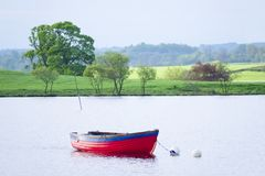 Le bateau à rames dans les rayures rouges et bleues d'été contre le soleil a allumé les champs verts dans la campagne rurale photos libres de droits