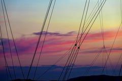 Le bateau à voile de silhouette mâte des cordes au coucher du soleil Image stock