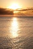 Le bateau à voile sur l'horizon s'est baigné dans les rayons du soleil Image libre de droits
