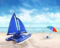 Le bateau à voiles de jouet sablent dedans avec la scène de plage Photos stock