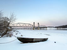Le bateau équipe le bateau sur la plage au coucher du soleil d'hiver avec le pont en train sur un fond Photo stock